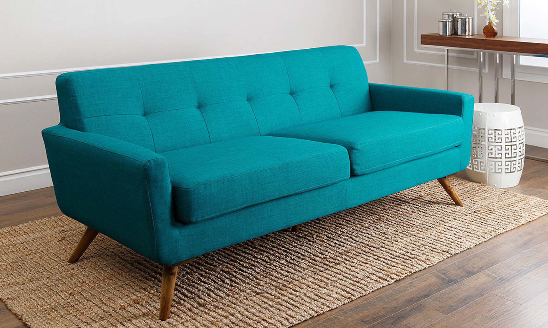 Mid-century modern sofa in teal upholstery with wood legs on tan rug