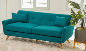 Mid-century modern sofa in teal upholstery with wood legs, button tufting and throw pillows in living room with plant