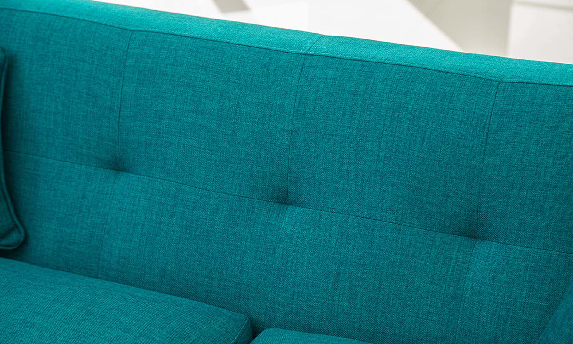 Close-up of button tufting on mid-century modern sofa in teal upholstery