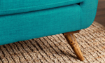 Close-up of wooden leg on mid-century modern sofa in teal upholstery