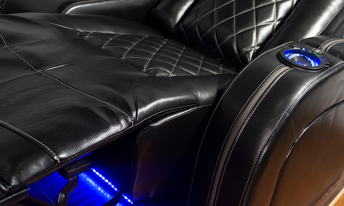 Close-up of power recliner on Transformer theater sofa with blue LED lights and storage in black top grain leather