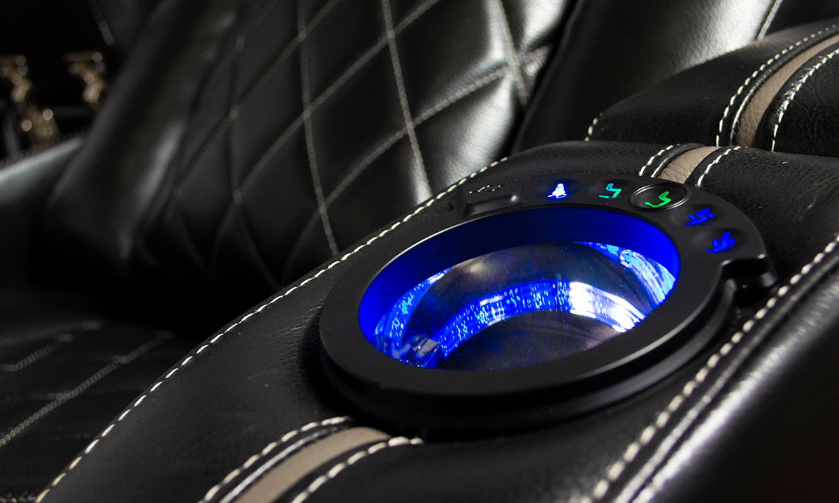 Closeup shot of illuminated cupholder on loveseat with blue LED light and storage in black top grain leather