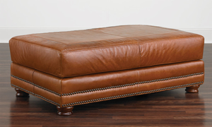 50-inch ottoman in cognac top-grain leather with nailhead trim and bun feet.