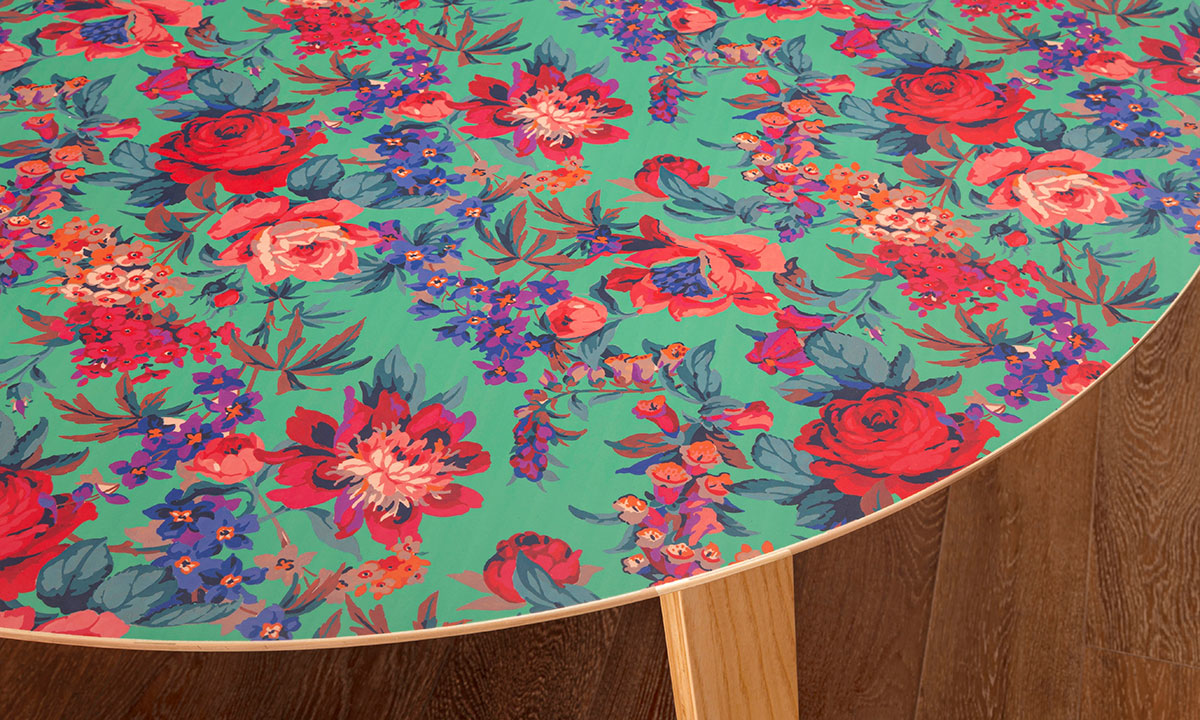 "Closeup of modern 51"" round dining table with green, pink and purple floral design and 4 wooden legs."