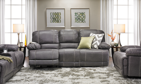 90-inch sofa with pillow top arms and dual power recliners in gray faux leather with contrast color stitching in living room