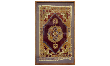 Framed antique handcrafted Turkish rug with floral medallion in deep wine tone with gold flowers.