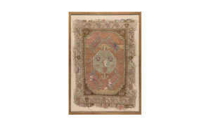 Framed antique Turkish rug with distressed medallion pattern with rosettes in rose and blue tones.