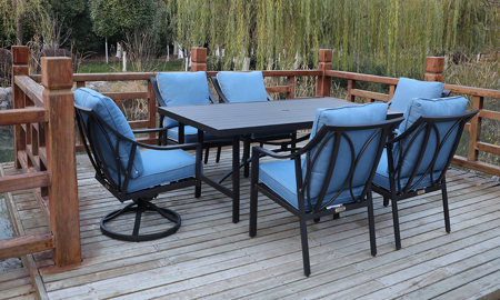 All-weather 7-piece outdoor dining set with 84-inch table, 4 chairs and 2 swivel rockers in aluminum with quick dry blue cushions on deck