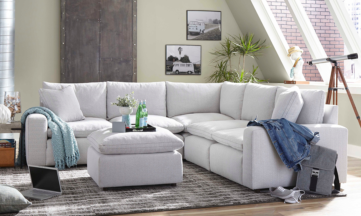 Modular grey fabric upholstered corner sectional with feather down blend cushion toppers.