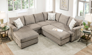 Tan fabric upholstered reversible chair sectional couch.