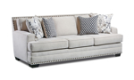 Cream-colored fabric upholstered sofa with four coordinating throw pillows and nail head trim.