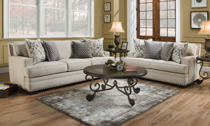 Two-piece living room set includes a cream-colored fabric couch and loveseat with coordinating toss pillows.
