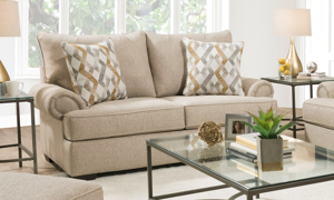 Traditional roll-arm sofa with beige-colored fabric upholstery and two matching throw pillows.
