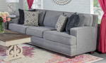 Grey fabric upholstered sofa with nail head trim and four coordinating throw pillows.