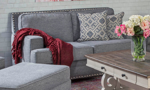 Grey fabric upholstered loveseat with two coordinating throw pillows.