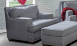 Oversized grey fabric upholstered armchair with nail head trim.