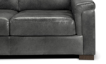Detail shot of the leg and cushions of the Medici Grey Leather Sofa showing the high-end tailoring, unique layover armrests and luxe grey leather upholstery.