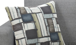 Detail of two included throw pillows featured a modern, abstract motif in a complimentary color palette.