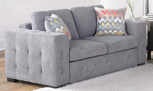 Angled shot of the Rowan Grey loveseat featuring a modern track arm profile and tufted tailoring.