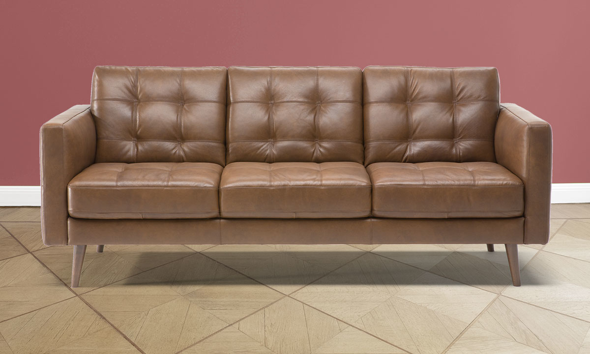 """83"""" wide brown leather couch from Natuzzi in a living room."""